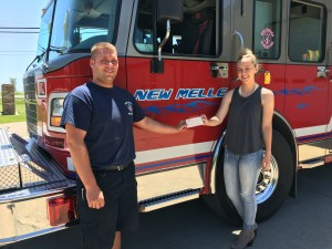 NMFR Firefighter Josh Ellis presents check to Madison Skambraks